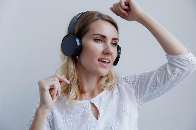 Mooi blond meisje met een koptelefoon. ze luistert graag naar muziek, zingt en heeft plezier.