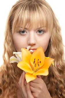 Mooi blond meisje met gele lelie op wit wordt geïsoleerd