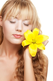Mooi blond meisje met gele lelie