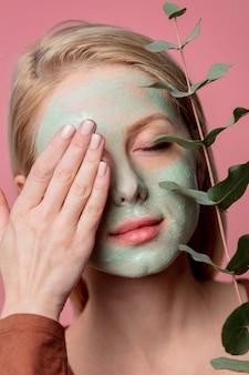 Mooi blond meisje met groen masker en eucalyptustak