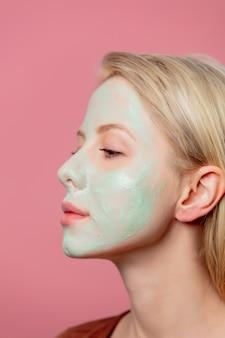 Mooi blond meisje met groen masker op haar gezicht