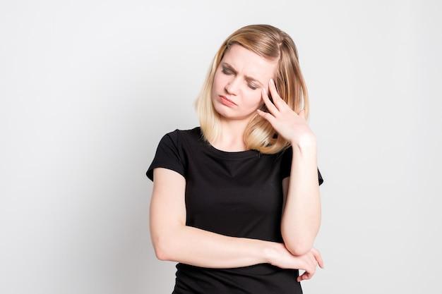 Mooi blond meisje met hoofd pijn