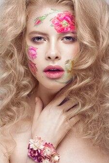 Mooi blond meisje met krullen en een bloemmotief op het gezicht. schoonheid bloemen.