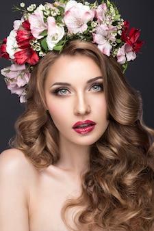 Mooi blond meisje met krullen en krans van paarse bloemen op haar hoofd.