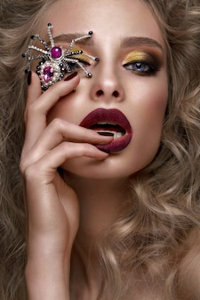 Mooi blond meisje met krullen, lichte make-up en designertoebehoren