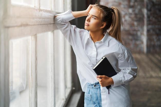 Mooi blond meisje met smartphone en notebook in haar handen.