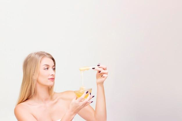 Mooi blond meisje op een shugaring-procedure. houdt een pasta in de hand om te shugaring en kijkt ernaar.