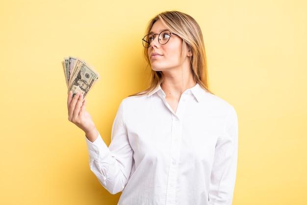 Mooi blond meisje op profielweergave denken, fantaseren of dagdromen. dollar biljetten concept