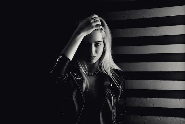 Mooi blond meisje, poseren naast de muur