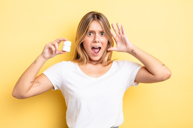 Mooi blond meisje schreeuwen met handen omhoog in de lucht. pillen fles concept