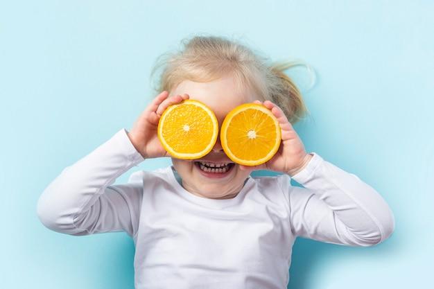 Mooi blond meisje sloot haar ogen met een gesneden sinaasappel terwijl ze op een blauw oppervlak lag