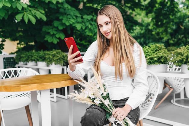 Mooi blond meisje zit aan tafel met een telefoon in zijn handen