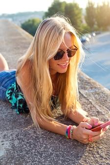 Mooi blond meisje zit op het dak met mobiele telefoon.