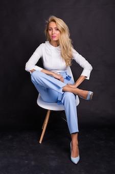 Mooi blond model in wit overhemd en spijkerbroek die op stoel voorbij zit