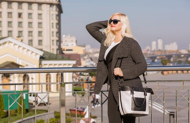 Mooi blond model loopt in grijze gebreide jas, draagt een zonnebril, houdt leren tas in handen