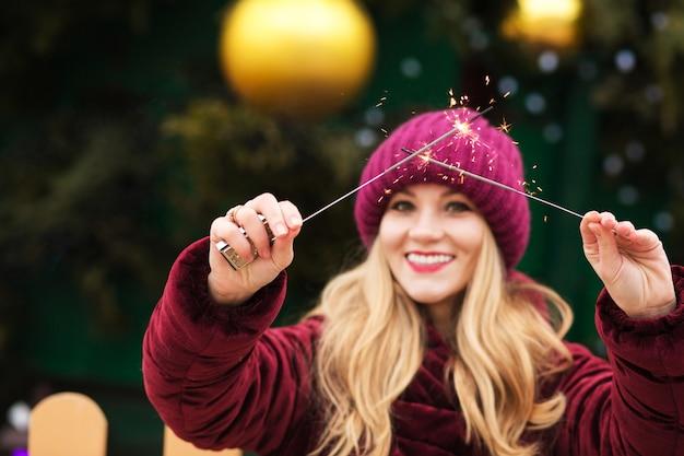 Mooi blond model met gloeiende bengaalse lichten bij de belangrijkste kerstboom in kiev. vervagingseffect