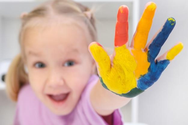 Mooi blond peutermeisje met kleurrijk geschilderd op haar handen, gelukkig lachend