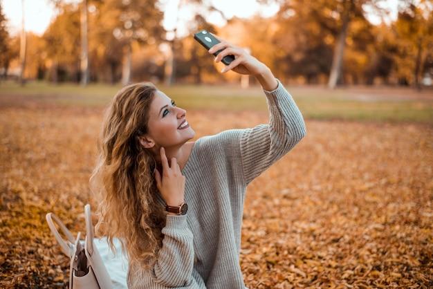 Mooi blondemeisje die de moderne zitting van de de herfstuitrusting in park in de herfst dragen die een selfie op smartphone nemen.