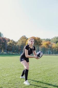 Mooi blondemeisje die een rugbybal vangen