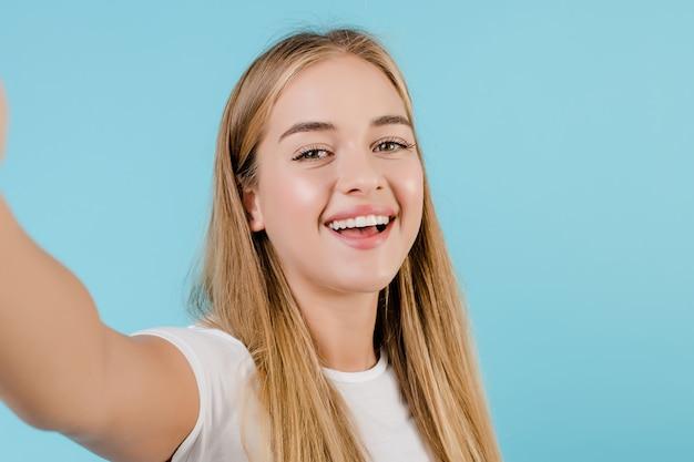 Mooi blondemeisje die selfie geïsoleerd over blauw maken