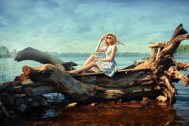 Mooi blondemeisje in een hoed en glazen die op drijfhout op riverbank zitten