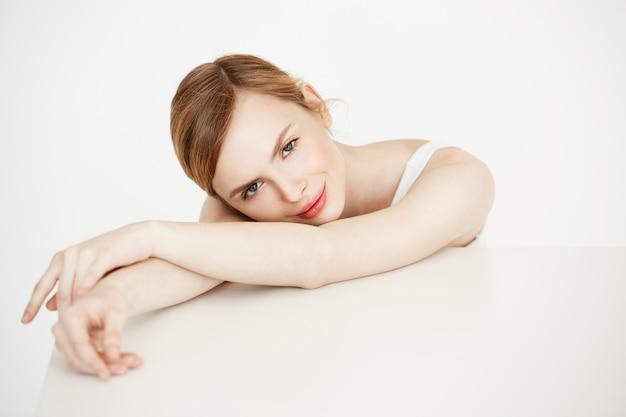 Mooi blondemeisje met perfecte schone huid het glimlachen zitting bij lijst. cosmetologie. gezichtsbehandeling.