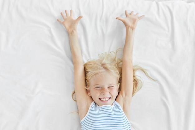 Mooi blondemeisje met sproeterige gezonde huid, die haar ogen met plezier sluit en zich in wit bed uitrekt, die zich verheugend aan nieuwe dag begint