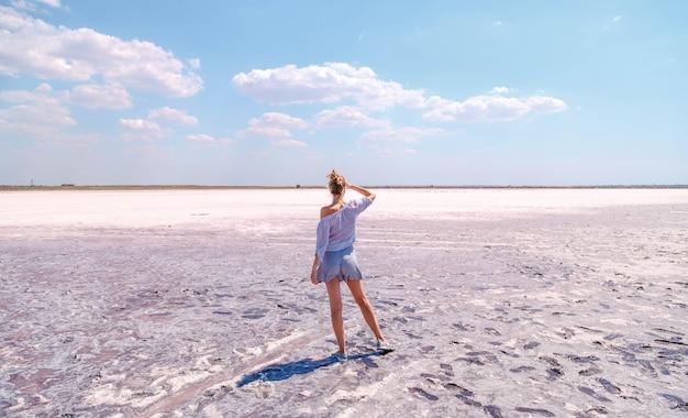 Mooi blondemeisje op een roze zout meer in de zomer