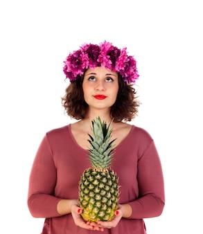Mooi bochtig meisje met een gebloemde hoofdtooiholding en een ananas