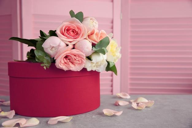 Mooi boeket bloemen op rode geschenkdoos
