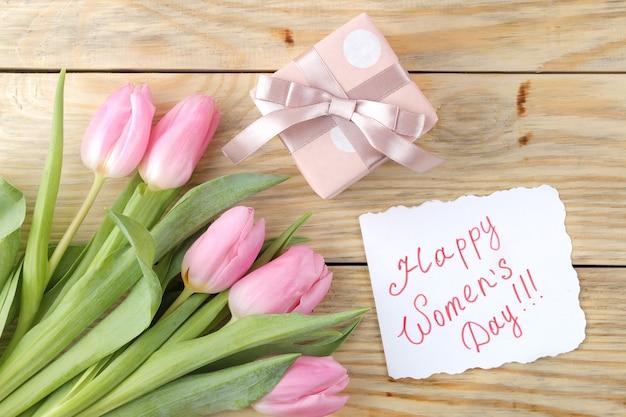 Mooi boeket bloemen van roze tulpen en tekst happy women's day op papier op een natuurlijke houten ondergrond