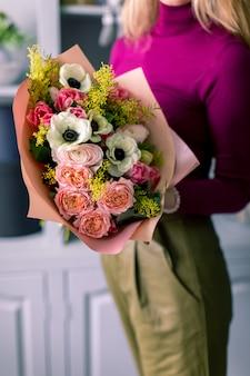 Mooi boeket gemaakt van verschillende bloemen in de hand van de jonge man. kleurrijke kleurenmix bloem.