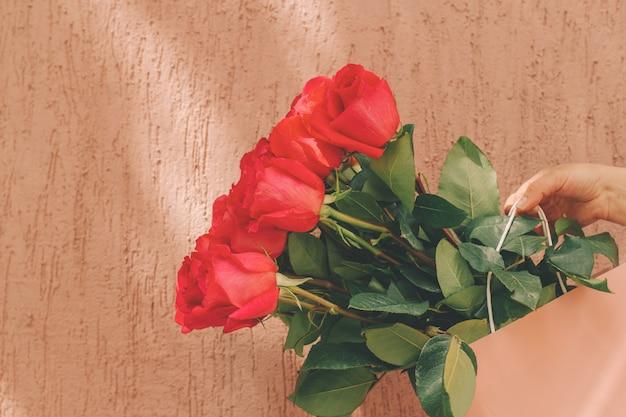 Mooi boeket rozen in een pastel roze pakket in handen van vrouwen tegen ruwe muur