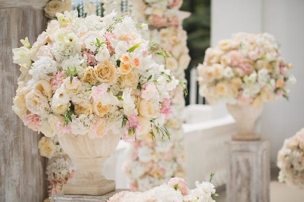 Mooi boeket rozen in een vaas op een achtergrond van een huwelijksboog. mooie opzet voor de huwelijksceremonie.