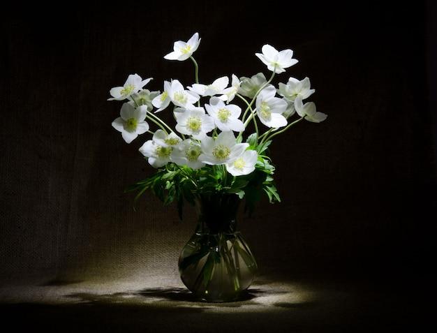 Mooi boeket tedere witte bloemen in transparante vaas bij plundering