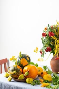 Mooi boeket van ambrosia, zinnia en takken van viburnum in een aarden pot, verse oogst van pompoenen op een tafel tegen een witte muur