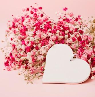 Mooi boeket van baby's-adembloemen met witte hartvorm op roze achtergrond