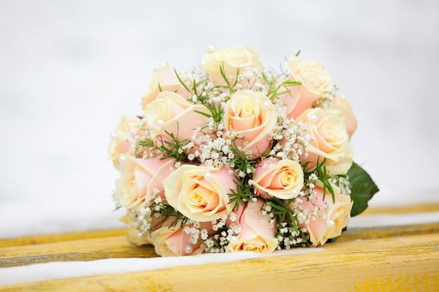 Mooi boeket van de bruid uitgevoerd van lichtbeige rozen en liggend op de sneeuwbank