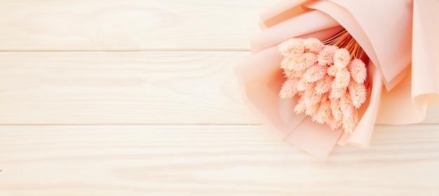 Mooi boeket van droge roze bloemen op een houten witte achtergrond.