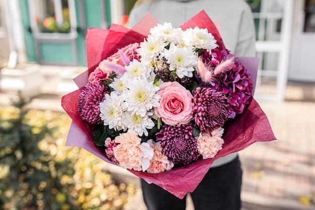 Mooi boeket van gemengde bloemen in handen van de vrouw. het werk van de bloemist bij een bloemenwinkel
