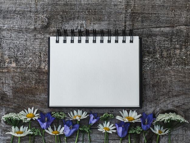 Mooi boeket van heldere bloemen en blocnote