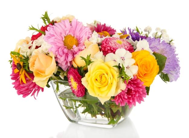 Mooi boeket van heldere bloemen in glazen vaas, op wit