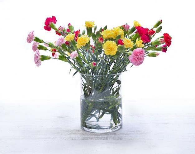 Mooi boeket van kleurrijke bloemen - anjer - in een glaskruik op geïsoleerd wit