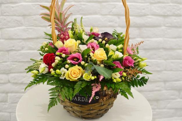 Mooi boeket van kleurrijke bloemen in de mand op tafel