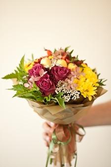 Mooi boeket van kleurrijke bloemen in een herfstkleuren in de hand van een man.