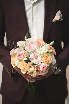 Mooi boeket van kleurrijke rozen in de handen van de bruidegom.