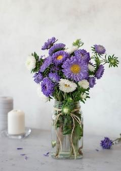 Mooi boeket van lila en witte bloemen in een glazen vaas