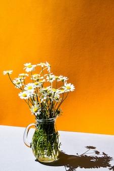 Mooi boeket van madeliefjes in glazen vaas op oranje en grijze tafel