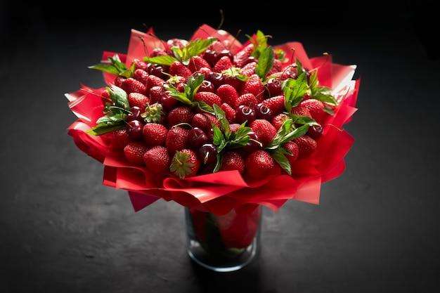 Mooi boeket van rijpe aardbeien en kersen op zwart