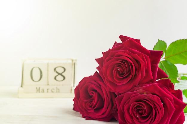 Mooi boeket van rode rozen en houten kubuskalender op een houten achtergrond. het concept van felicitaties op 8 maart of wooman's dag.